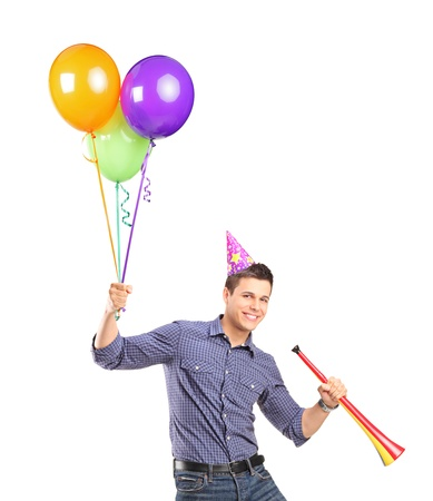 Portrait of a happy male holding balloons and a horn isolated on white background photo