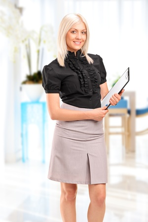 Portrait of a young businesswoman holding a clipboard and posing in the office