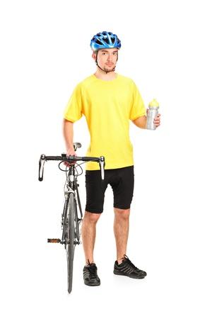ciclo del agua: Retrato de cuerpo entero de un ciclista posando junto a una bicicleta y con una botella aisladas sobre fondo blanco Foto de archivo