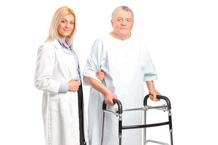 A female doctor or nurse helping a senior patient to use a walker isolated on white background photo