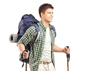 backpacking: A hiker with backpack holding hiking poles and posing isolated on white background
