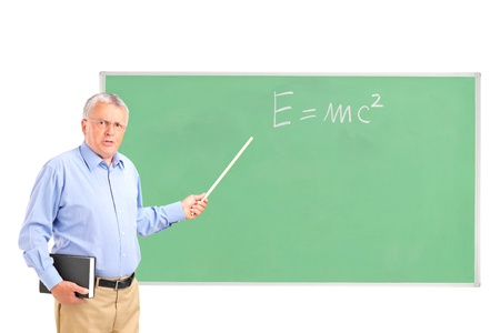 An angry mature teacher with a book in his hand and chalkboard in the background photo