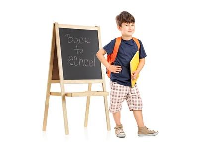 mochila escolar: Retrato de cuerpo entero de un niño de la escuela con mochila posando junto a una pizarra sobre fondo blanco Foto de archivo