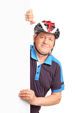 Portrait of a senior bicyclist wearing helmet and posing behind a white panel isolated on white background photo