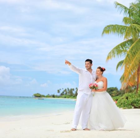 A bride holding a bouquet and groom looking towards, shot on a beach at Kuredu island, Maldives, Lhaviyani atoll photo
