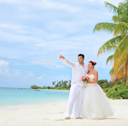newlyweds: A bride holding a bouquet and groom looking towards, shot on a beach at Kuredu island, Maldives, Lhaviyani atoll Stock Photo