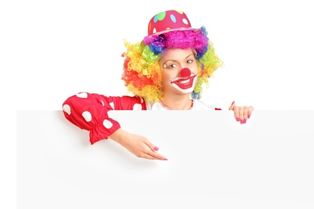 wigs: A female clown with happy joyful expression on her face posing behind a white panel isolated on white background Stock Photo