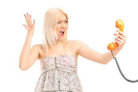 A shocked blond woman screaming on a phone isolated against white background photo