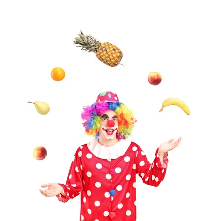 A smiling clown juggling fruits isolated against white background photo