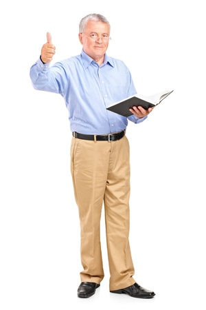 Full length portrait of a male teacher holding a book and giving a thumb up isolated on white background photo