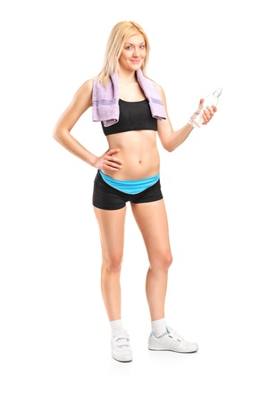 Full length portrait of an attractive sportswoman with a bottle of mineral water posing after a training isolated on white background photo