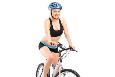 Smiling female biker with helmet sitting on a bike isolated against white background Stock Photo - 14257235