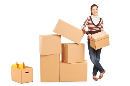 Smiling woman holding a box and many other boxes around her isolated on white background photo