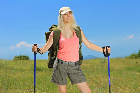 A smiling woman with backpack and hiking poles posing outdoor photo