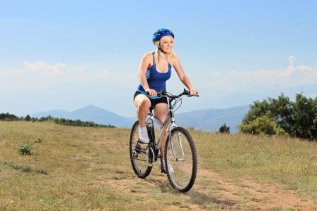 A young female biking a mountain bike outdoors photo