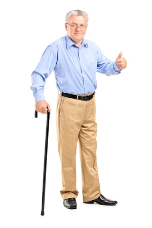 Full length portrait of a senior man holding a cane and giving thumb up isolated on white background photo