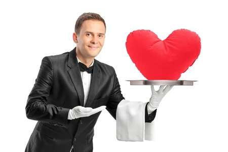 sirvientes: Un mayordomo que sostiene una bandeja con un objeto en forma de corazón rojo en él aislados sobre fondo blanco Foto de archivo