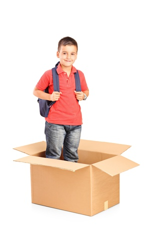 A child with backpack standing in a cardbox isolated on white background Stock Photo - 14286148