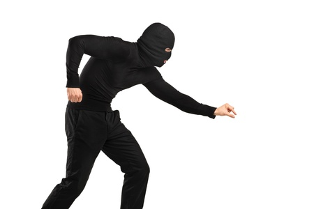 A man in robbery mask trying to steal something isolated on white background Stock Photo - 14286053