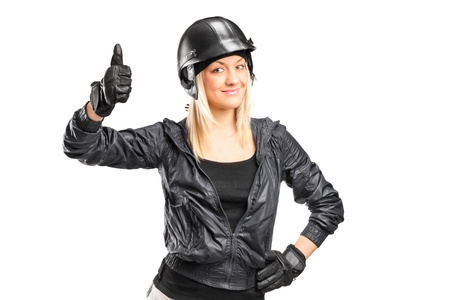 A smiling female motorcycler giving a thumb up isolated on white background photo