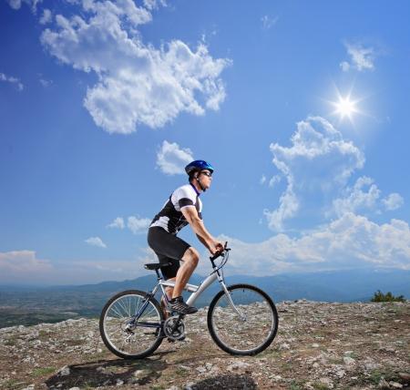 andando en bicicleta: Un ciclista joven en bicicleta una bicicleta de monta�a en un d�a soleado Foto de archivo