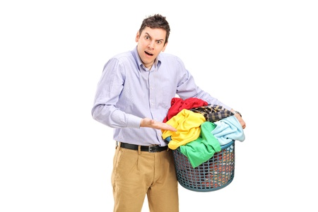 A young man holding a laundry basket and gesturing isolated on white background Stock Photo - 14286188