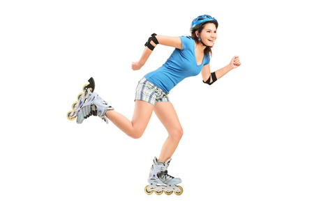 Full length portrait a smiling girl on rollers skating isolated on white background photo