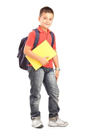 mochila escolar: Retrato de cuerpo entero de un niño de la escuela feliz con la mochila la celebración de un bloc de notas aisladas sobre fondo blanco