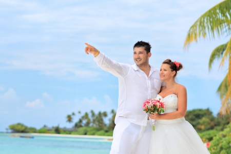 wedding beach: A bride with a bouquet of flowers and groom looking towards, shot on a beach in Kuredu resort, Maldives island, Lhaviyani atoll Stock Photo