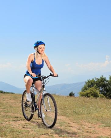 bicyclist: A female biker biking a mountain bike on a sunny day