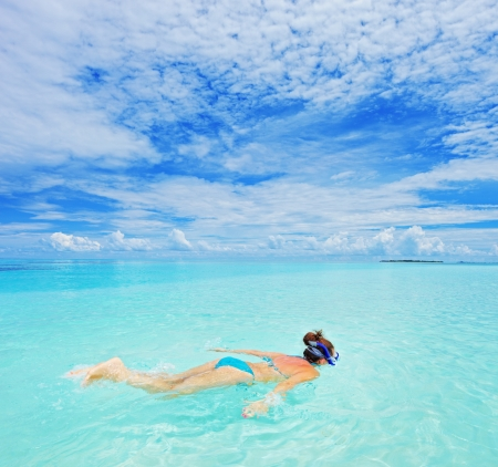 A woman with snorkeling mask diving in Kuredu resort, Maldives island, Lhaviyani atoll photo