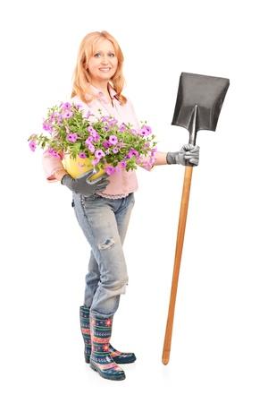 horticulturist: Full length portrait of a female gardener holding  flowers and a shovel isolated on white background