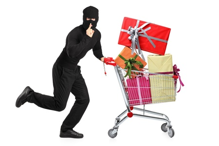 Full length portrait of a robber pushing a cart with finger on his lips gesturing silence isolated on white background photo