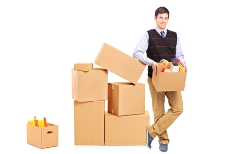 Full length portrait of a smiling male holding a box and many other boxes around isolated on white background photo