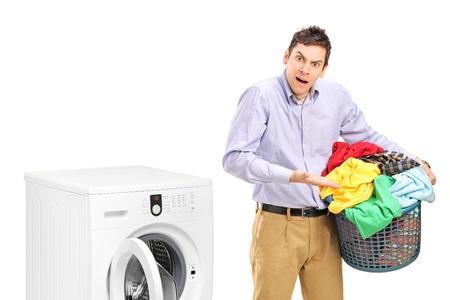 lavadora con ropa: El hombre joven sosteniendo un cesto de la ropa y hacer gestos cerca de una máquina de lavar aisladas sobre fondo blanco