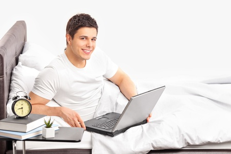 A portrait of a smiling man lying on a bed and working on a laptop photo