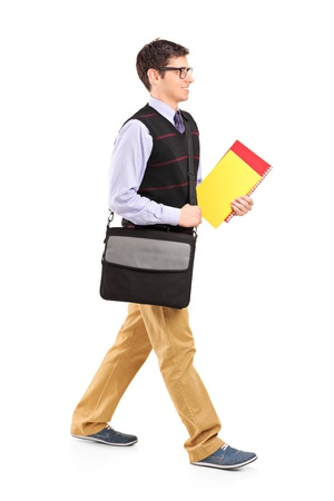 Full length portrait of a student walking with notebooks in his hand isolated on white background photo
