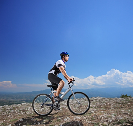Male bicyclist riding a bike on a mountain photo