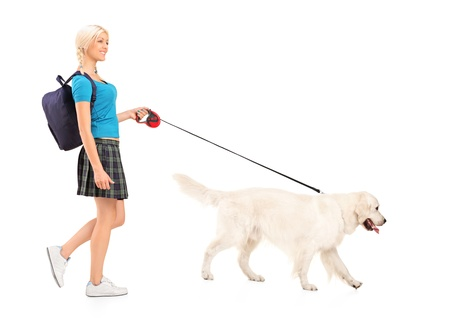 Full length portrait of a female student walking a dog, isolated on white background photo