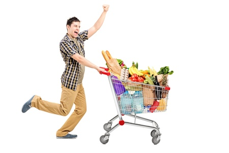 full shot: Full length portrait of a happy man pushing a shopping cart, isolated on white background