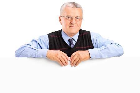 Mature man posing behing white panel, isolated on white background photo