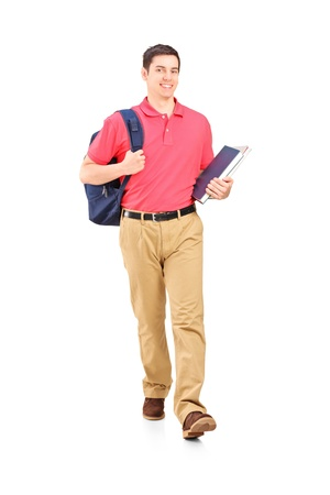 Full length portrait of a male student walking, isolated on white background photo