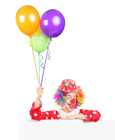 A male clown with happy joyful expression on his face posing behind a panel and holding balloons isolated on white background photo