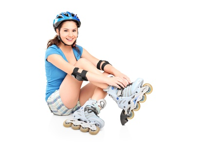rollerblade: A girl putting on roller skates isolated against white background Stock Photo