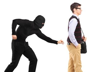 Een zakkenroller met masker proberen om een portefeuille op een witte achtergrond te stelen Stockfoto