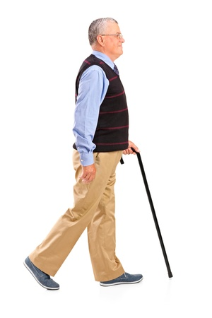 persona caminando: Retrato de cuerpo entero de un hombre mayor caminando con bastón sobre fondo blanco Foto de archivo