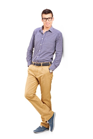 casual clothing: Full length portrait of a young male leaning against wall isolated on white background Stock Photo