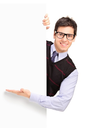 welcome people: Smiling handsome male posing behind a blank panel isolated on white background