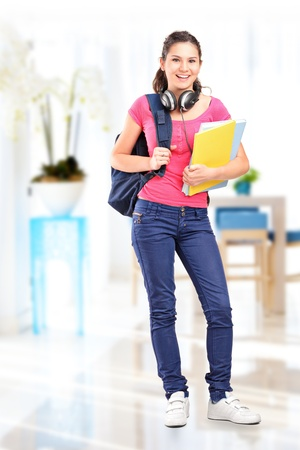 Full length portrait of a female student with headphones posing Stock Photo - 14615237