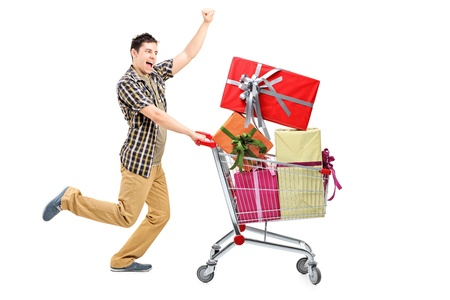 Full length portrait of a happy man pushing a shopping cart full of gifts, isolated on white background photo